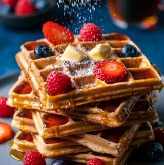 Powdered sugar sprinkling over a stack of vegan waffles.