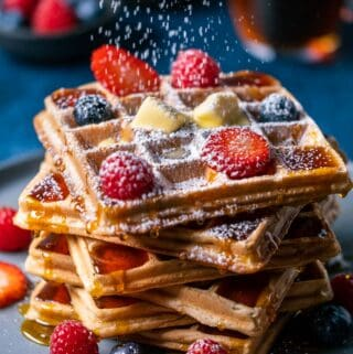 Powdered sugar sprinkling down over a stack of waffles.