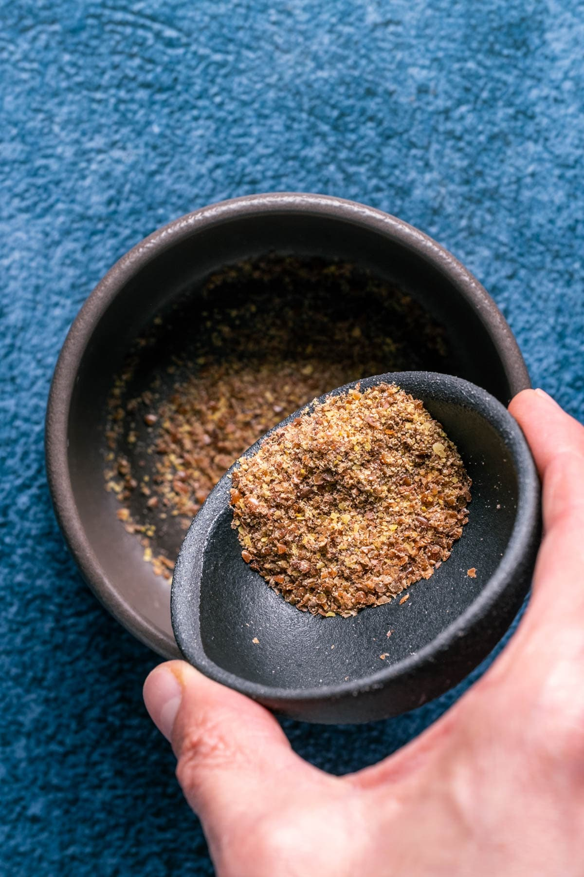 Photo of adding ground flaxseeds to a bowl.