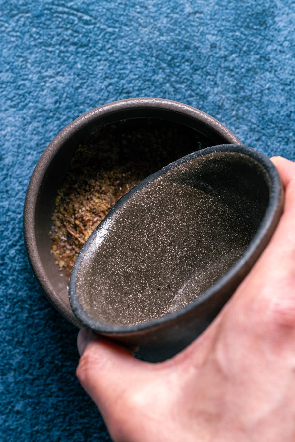 Photo of adding hot water to the ground flaxseeds in a bowl.
