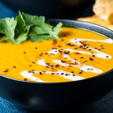 Thai sweet potato soup in a black bowl.