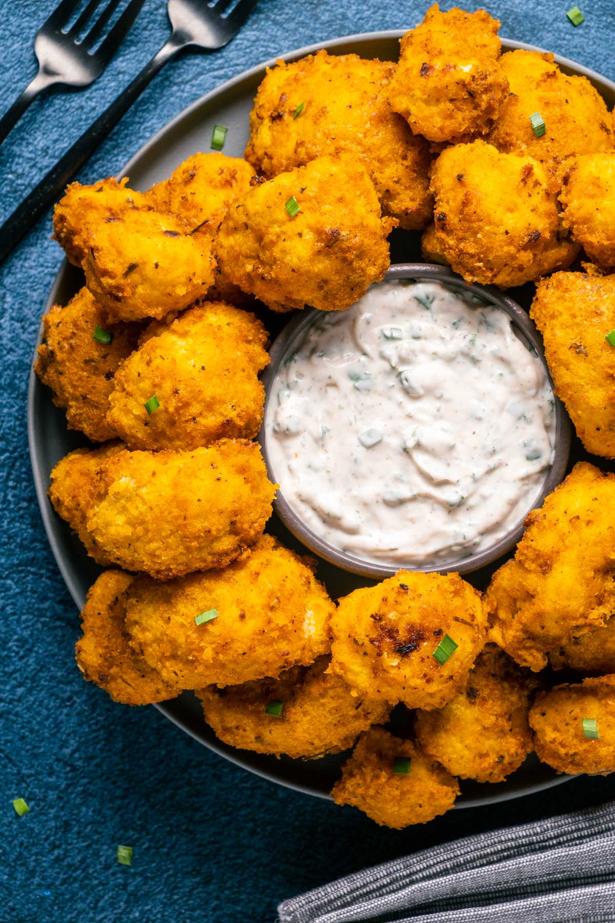 Vegan buffalo cauliflower on a plate with a bowl of ranch dressing.