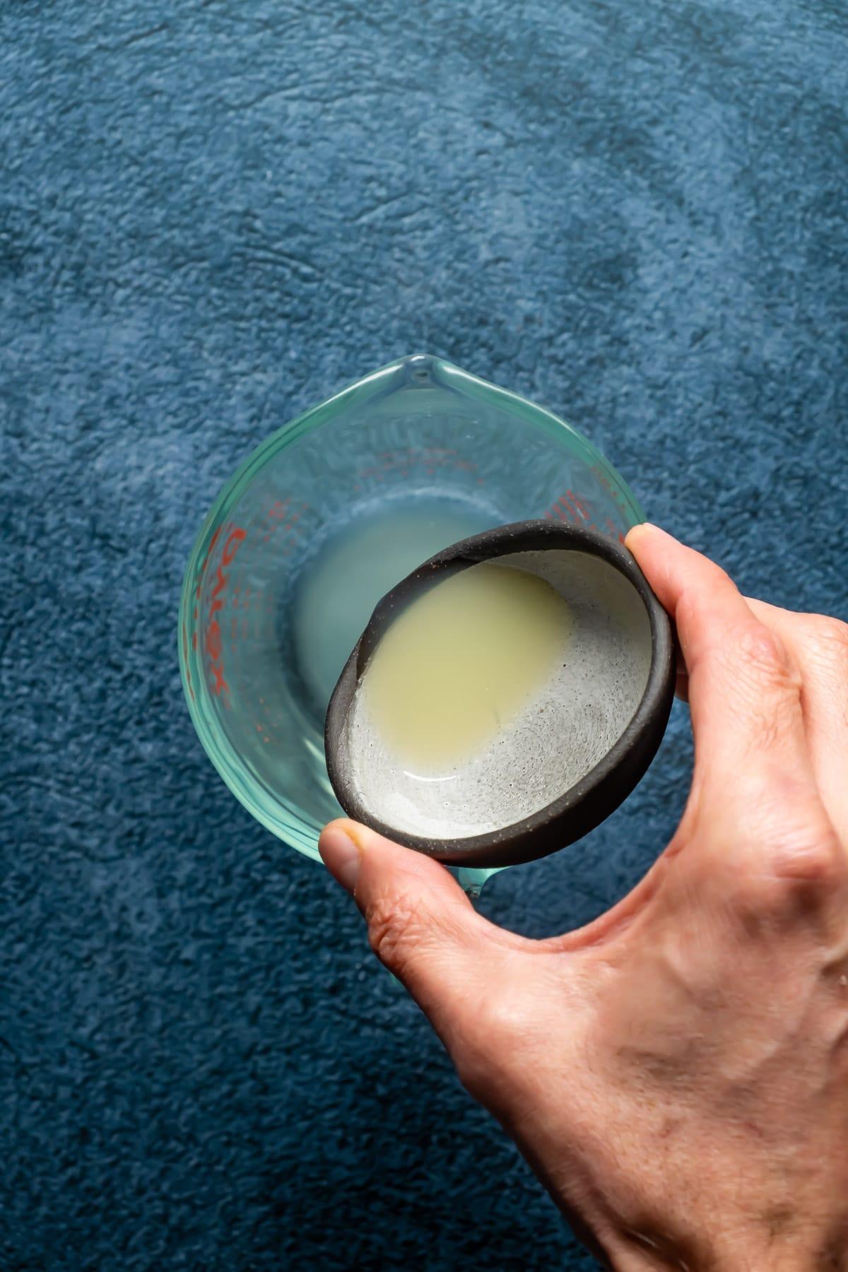 Pouring lemon juice into a glass jug.