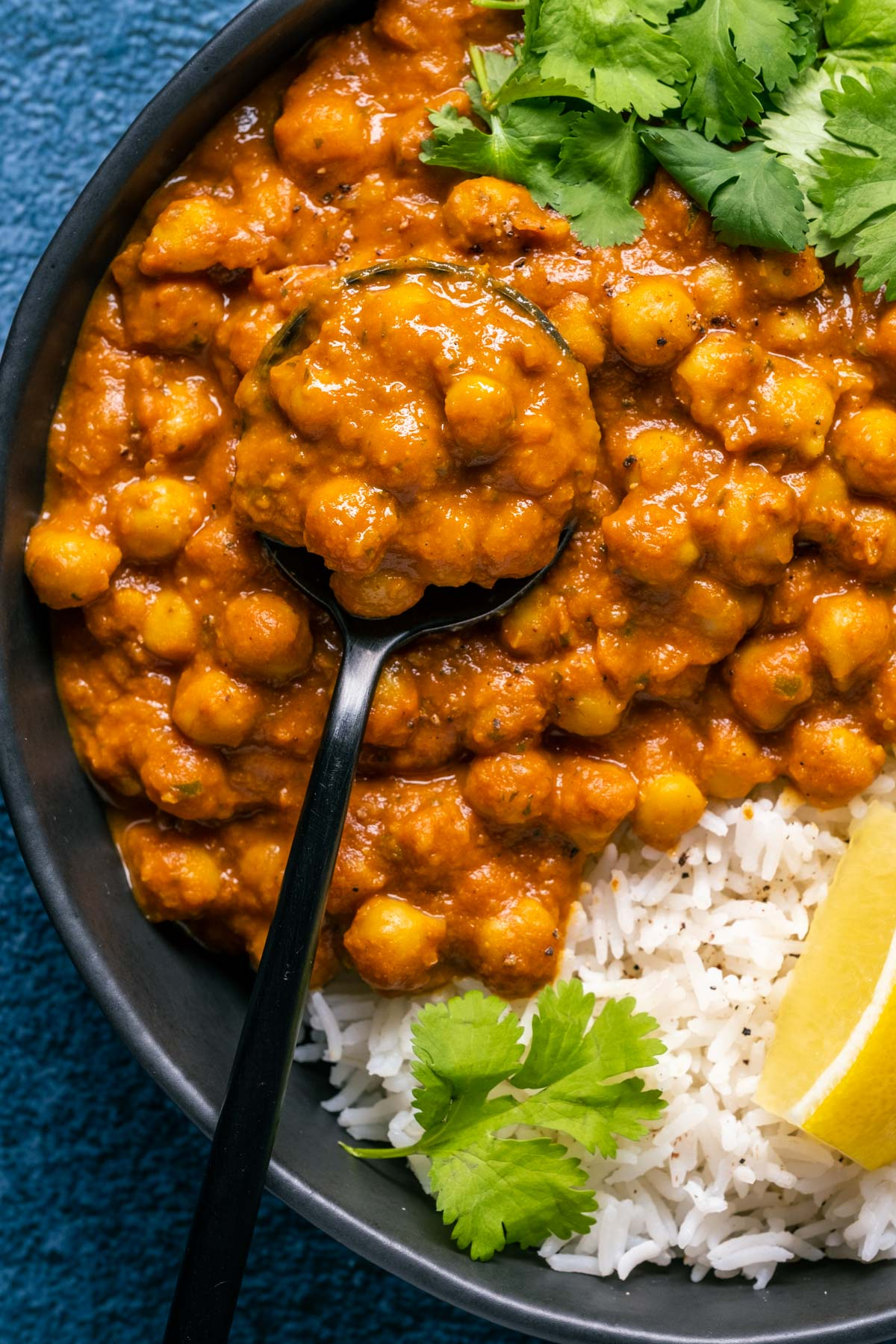 Vegan chana masala with rice, cilantro and fresh lemon in a black bowl with a spoon.
