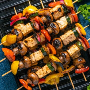 Vegan kebabs stacked up on a grill.