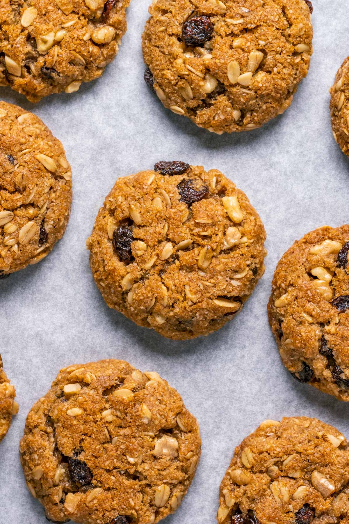 Vegan oatmeal raisin cookies on a parchment lined baking tray.